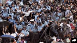 Polisi anti huru-hara Hong Kong menjaga komplek pemerintahan dari demonstran pro demokrasi.
