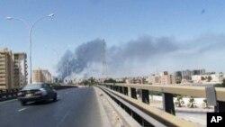 Khói bốc lên từ hướng sân bay Tripoli trong một cuộc giao tranh giữa các nhóm dân quân, ngày 13 tháng 7, 2014.