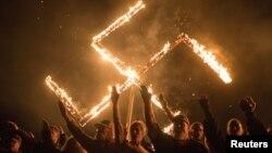 Arhiv - Pristalice nacionalsocijalističkog pokreta, političke grupe bijelih nacionalista, u stavu nacističkog pozdrava dok učestvuju u paljenju svastike na nepoznatoj lokaciji u Georgiji, SAD.