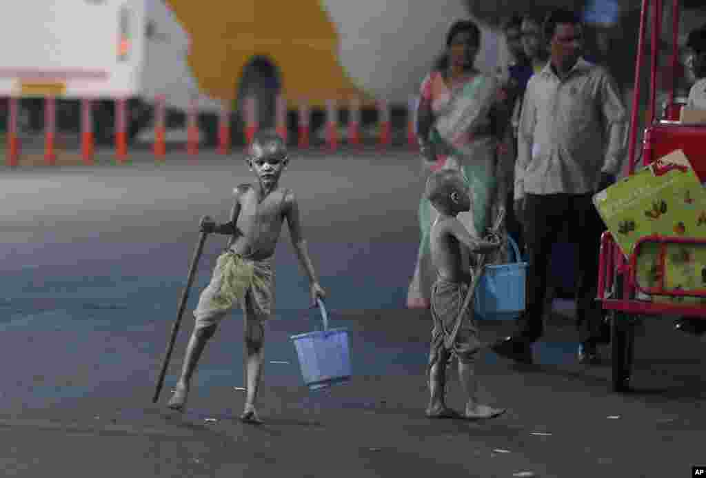 Young boys with their bodies painted and dressed as Mahatma Gandhi seek alms at a traffic intersection in Hyderabad, India.