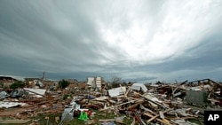 Storm clouds build in the distance beyond tornado-ravaged homes in Moore, Oklahoma, May 21, 2013.