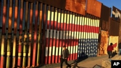 FILE - People pass graffiti along the border structure in Tijuana, Mexico, Jan. 25, 2017.