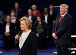 Democratic presidential nominee Hillary Clinton, left, talks as Republican presidential nominee Donald Trump watches her during the second presidential debate at Washington University in St. Louis, Sunday, Oct. 9, 2016.