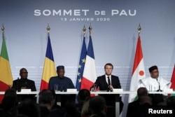 FILE - French President Emmanuel Macron, Mali's President Ibrahim Boubacar Keita, Niger President Mahamadou Issoufou, and Chad's President Idriss Deby, deliver a news conference at the G5 Sahel summit in Pau, Jan. 13, 2020.