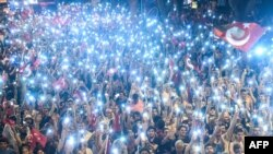 FILE - Supporters use flashlights on their cell-phones as they listen to presidential candidate of Turkey's main opposition Republican People's Party (CHP) Muharrem Ince (unseen) during an election campaign rally in Istanbul on June 9, 2018.
