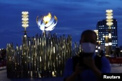 FILE - A man wearing a protective mask stands in front of the second Paralympic flame cauldron at Ariake Yume-no-Ohashi Bridge, a day after the official opening of Tokyo 2020 Paralympic Games, in Tokyo, Japan, Aug. 25, 2021.