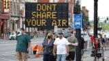 FILE - A sign encouraging the wearing of masks and keeping social distancing stands at a street corner in downtown Nashville, Tenn., Aug. 5, 2020.