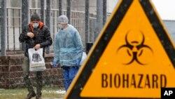 Seorang petugas medis dan seorang pria berbincang dekat rumah sakit isolasi Botkin, yang menjadi tempat perawatan diduga pasien virus corona, di St.Petersburg, Rusia, 16 Maret 2020.