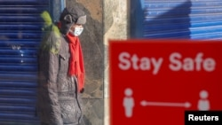 A person wearing a protective mask walks near a social-distancing sign, amid the outbreak of the coronavirus disease, in Coventry, Britain, Oct. 25, 2020.