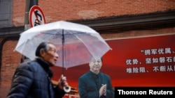 A man walks with an umbrella past a picture of Chinese President Xi Jinping on a street ahead of the National People's Congress (NPC), in Shanghai