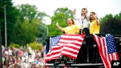Olympian Sunisa Lee, center, waves from a St. Paul fire truck with her mom Yeev Thoj, left, and sister Shyenne Lee as fans cheer for her along the White Bear Ave. parade route, Sunday, Aug. 8, 2021, in St. Paul, Minn. Minnesota celebrated the Olympic…