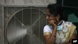 Seorang perempuan berdiri di depan AC untuk mendinginkan badannya pada saat suhu udara sangat panas di Hyderabad, negara bagian Telangana, India, 31 Mei 2015 (Foto: dok).