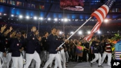 Multi-gold medal winner in swimming Michael Phelps carries the flag of the United States as he leads the U.S. team during the opening ceremony for the 2016 Summer Olympics in Rio de Janeiro, Brazil, Aug. 5, 2016.