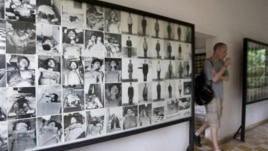 A tourist walks past photos of former prisoners displayed at Tuol Sleng genocide museum, a former Khmer Rouge prison known as S-21, in Phnom Penh.