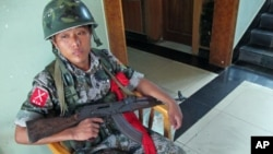 A soldier guards the Laiza Hotel, where the Kachin Independence Organization holds meetings, Laiza, Burma, August 2011.