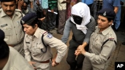 Perempuan warga Swiss (tengah, ditutupi wajahnya) dikawal polisi India setelah menjalani pemeriksaan di rumah sakit di Gwalior, India usai kasus pemerkosaan oleh lima pria (16/5).