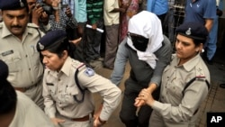 A Swiss woman, center, who, according to police, was gang-raped while touring by bicycle with her husband, is escorted by policewomen for a medical examination at a hospital in Gwalior, India, March 16, 2013.