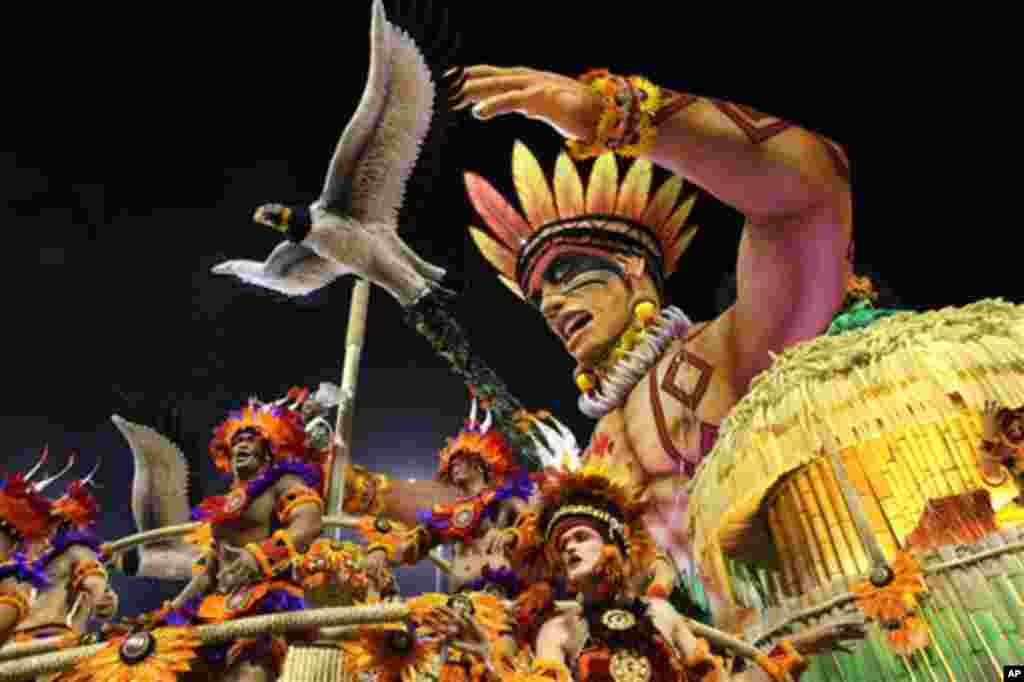 Carnival dancers perform on a float during a parade by the Perola Negra samba school in Sao Paulo, Brazil, early Sunday Feb. 19, 2012.