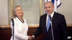 Menteri Luar Negeri AS, Hillary Clinton (kiri) berjabat tangan dengan PM Israel Benjamin Netanyahu di kantornya di Yerusalem (16/7).