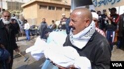 Un hombre carga parte de los restos de una víctima luego de protestas en Benghazi.