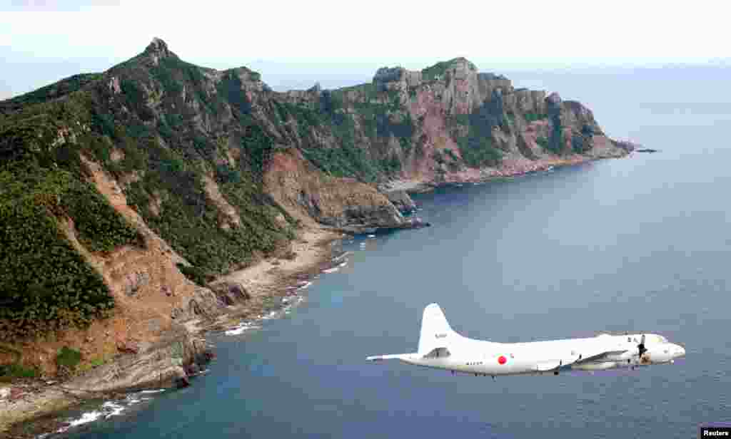 Japan Maritime Self-Defense Force's PC3 surveillance plane flies above Uotsuri Jima/Diaoyu Dao Island, October 13, 2011.
