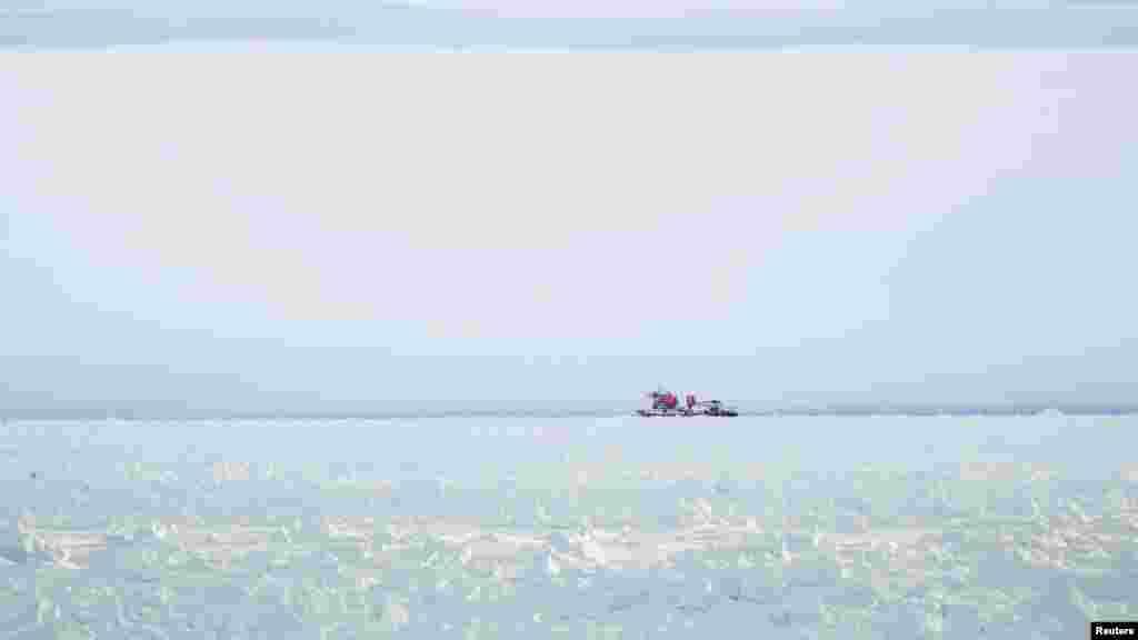 Kapal pemecah es Xue Long (Naga Salju) yang berada di atas tumpukan es tidak dapat mencapai kapal Rusia yang terperangkap di Antartika Timur, MV Akademik Shokalskiy, sekitar 185 kilometer sebelah timur stasiun Antartika Perancis Dumont D'Urville.