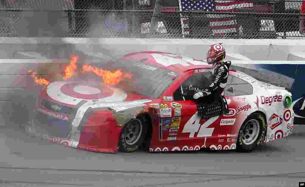 Kyle Larson exits his car as it catches fire after a crash in Turn 4 during the NASCAR Sprint Cup Series Pure Michigan 400 auto race at Michigan International Speedway in Brooklyn, Michigan, USA, Aug. 17, 2014.
