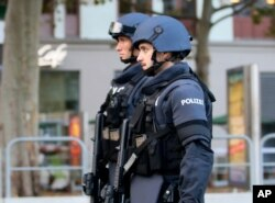After a shooting armed police officers patrol on a street at the scene in Vienna, Austria, Tuesday, Nov. 3, 2020.