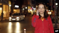 Dutch-Turkish journalist Ebru Umar talks on her mobile phone in Kusadasi, Turkey, Monday, April 25, 2016. Umar, a columnist for The Netherlands' Metro newspaper, has been barred from leaving Turkey.