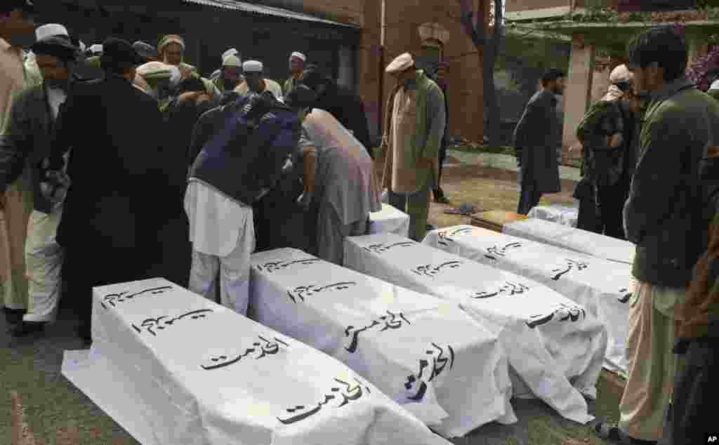 People stand near coffins of people killed in a bomb blast in the Pakistani tribal area of Khyber, December 17, 2012.
