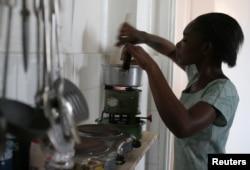 A Tanzanian woman uses a kerosene stove to prepare a meal in the capital Dar es Salaam, Sept. 28, 2006.