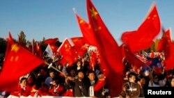资料照:中国在新西兰的支持者在澳大利亚堪培拉迎接奥运火炬的仪式上挥舞中国国旗。(2008年4月24日)