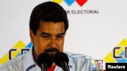委内瑞拉代总统马杜罗在记者会上手捧已故总统查韦斯相片