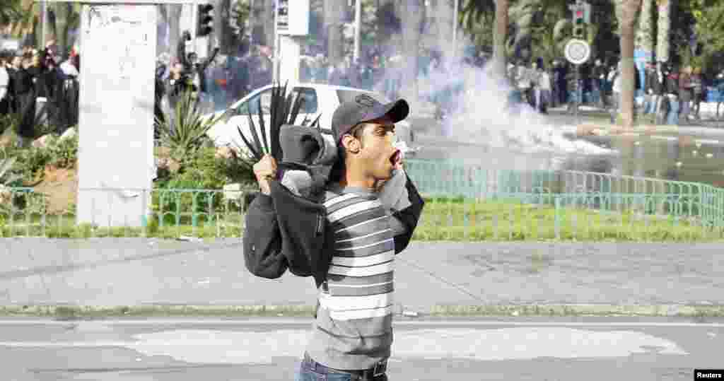 A protester gestures to police during clashes in Tunis, Feb. 6, 2013.