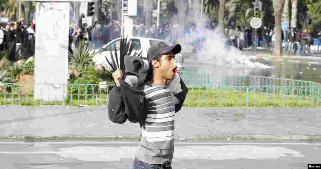 2013年2月6日在突尼斯发生警民冲突之际,一名抗议者对警察做手势。