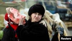 在基輔獨立廣場,一位支持與歐盟融合的反政府示威者帶著醜化俄羅斯總統普京的面具試圖親吻一名女士。(2013年12月22日)