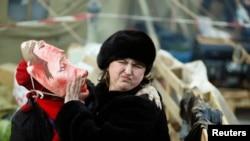 在基辅独立广场,一位支持与欧盟融合的反政府示威者带着丑化俄罗斯总统普京的面具试图亲吻一名女士。(2013年12月22日)