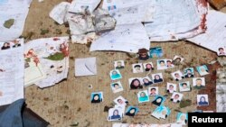 Blood-stained national ID papers and voters' photos are seen on the ground outside a voter identification card center after a suicide attack in Kabul, April 22, 2018.