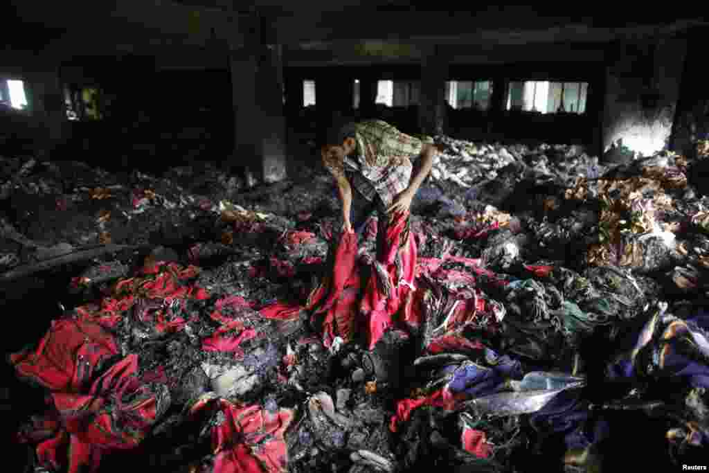A garment worker inspects a factory after a fire, Dhaka, Bangladesh, May 9, 2013.
