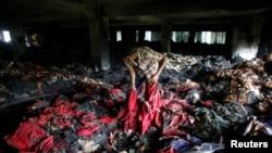 Seorang pekerja pabrik garmen melakukan inspeksi setelah musibah kebakaran di Dhaka, Bangladesh (9 Mei 2013).