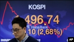 A currency trader walks by a screen showing the Korea Composite Stock Price Index (KOSPI) at the foreign exchange dealing room in Seoul, South Korea, Friday, March 20, 2020. Asian stock markets were mostly higher Friday after modest Wall Street…