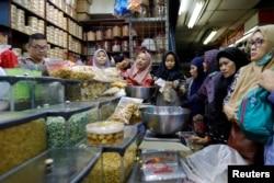 Ibu-ibu belanja makan ringan di sebuah pasar di Jakarta untuk menyambut Idul Fitri, 3 Juni 2019. (Foto: Reuters)