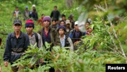 Montagnard hill tribesmen walk towards the main road after emerging from dense forest 70 km (43 miles) northeast of Ban Lung, located in Cambodia's northeastern province of Ratanakiri, file photo.