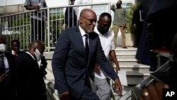 El nuevo primer ministro de Haití, Ariel Henry, sube escaleras acompañado de escoltas después de ser designado al cargo, el 20 de julio de 2021, en Puerto Príncipe.