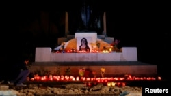 FILE - An activist places candles and flowers on the Great Siege monument, after rebuilding a makeshift memorial to assassinated anti-corruption journalist Daphne Caruana Galizia, in Valletta, Malta, Nov. 16, 2018.