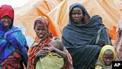 图为一个流离失所的索马里家庭8月2日站在临时帐篷外的雨中