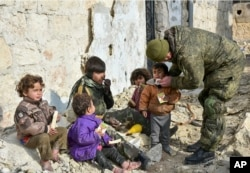 This undated handout photo released by the Russian Defense Ministry claims to show a Russian military engineer distributing juice to local children in Aleppo, Syria.