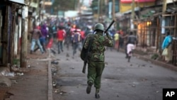 FILE - Opposition supporters run away from police during clashes after the election commission announced results from the Oct. 26 vote in the Kibera area of Nairobi, Kenya, Oct. 30, 2017.