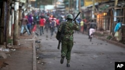 FILE - Opposition supporters run from police during clashes after the election commission announced results from the Oct. 26 vote in the Kibera area of Nairobi, Kenya, Oct. 30, 2017.