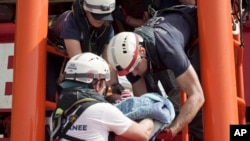 A newborn baby is carried onto the Ocean Viking humanitarian rescue ship after a rescue operation some 53 nautical miles (98 kilometers) from the coast of Libya in the Mediterranean Sea, Tuesday, Sept. 17, 2019.